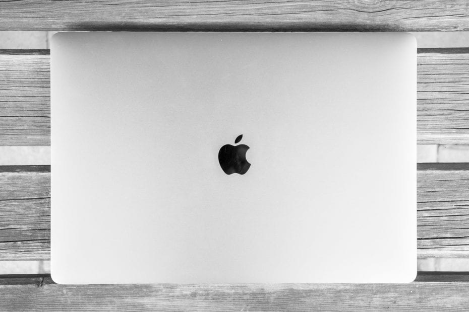 gray mac with the apple logo on a gray wooden surface